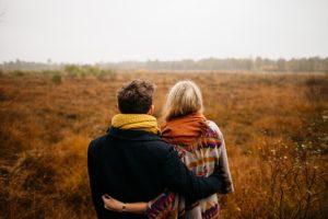 草原に座るカップルの写真