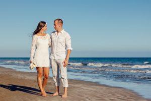 浜辺に立つカップルの写真